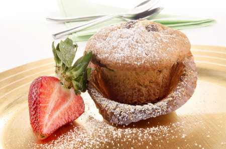 muffin with powdered sugar and strawberry on a plate photo