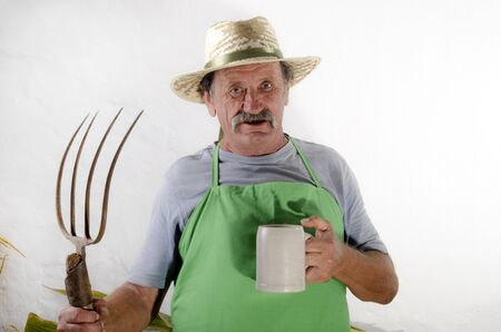 organic farmer with a pitchfork and a beer mug having a drink during his break photo