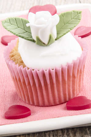 valentine cupcake with white rose and green leaves photo