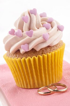 valentine cupcake with pink sugar hearts and golden rings photo