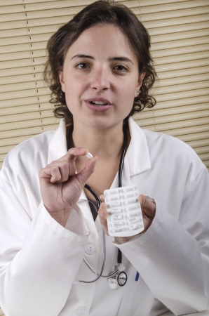 female medical staff holding a tablet and a tablets package photo