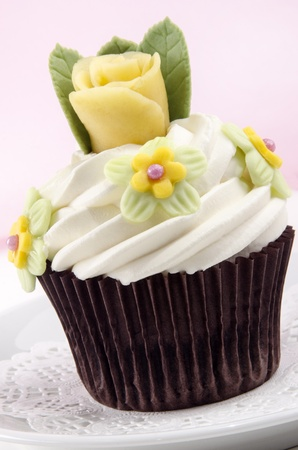 chocolate cupcake with butter cream and yellow rose photo