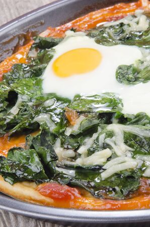 fresh baked pizza with spinach and fried egg photo