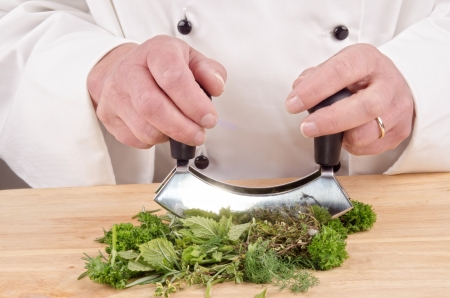 Fresh herbs are finely chopped with a herb cutter photo