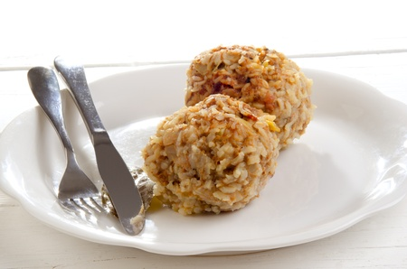 two meatballs with rice on a white plate photo