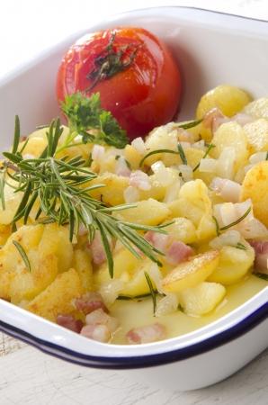 oven potatoes: baked potato with rosemary, bacon and tomato Stock Photo