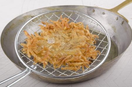 papas doradas: hash brown se saca de un recipiente de bronce