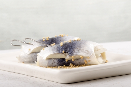 mustard seed: pickled herring with mustard seed on a plate