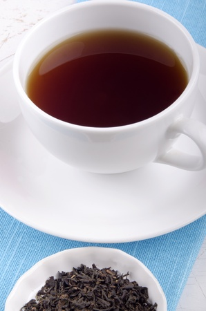 english breakfast tea: english breakfast tea in a white cup and some loose tea