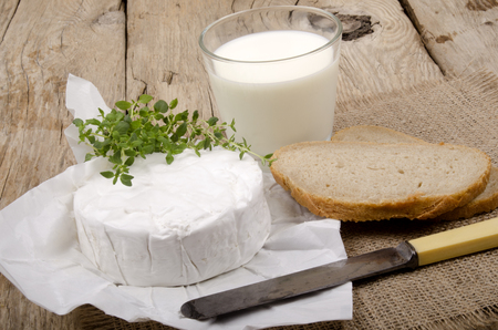 french brie camembert with thyme, bread and milk on a country house kitchen table photo
