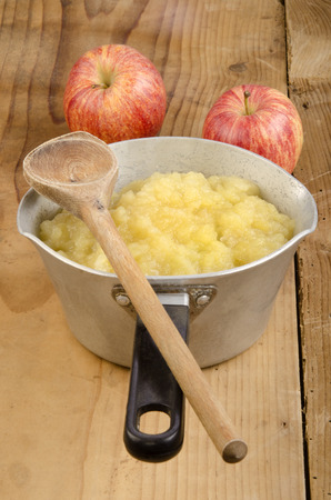freshly home made apple compote and a wooden spoon photo
