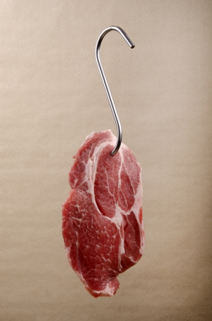 one slice raw pork meat on a butcher hook photo