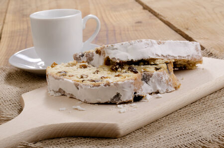 two slice christmas stollen with powdered sugar on a wooden board photo
