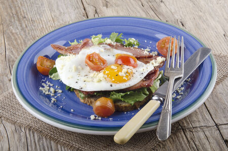 breakfast with bacon, fried egg and grilled tomato photo