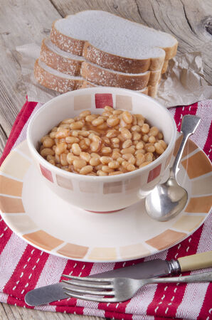 traditionally irish: baked beans in a bowl with sliced bread  Stock Photo