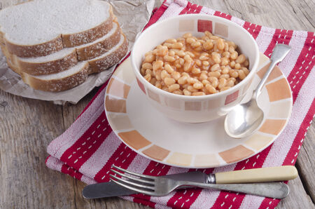 baked beans in a bowl with sliced bread  photo