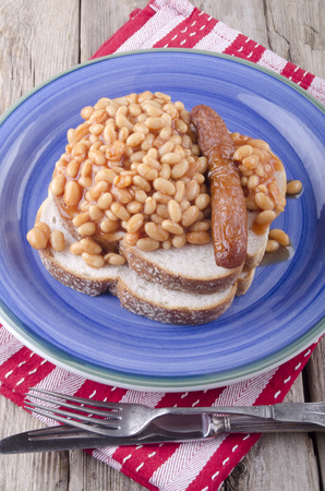 traditionally irish: baked beans, pork sausage and bread on a blue plate