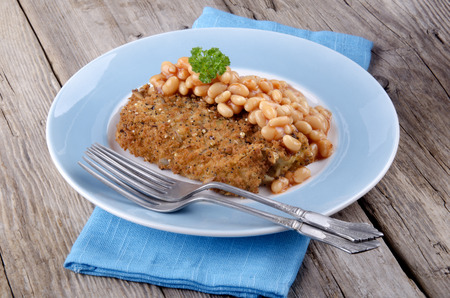 traditionally irish: baked beans and cod fillet in bread crumbs on a plate