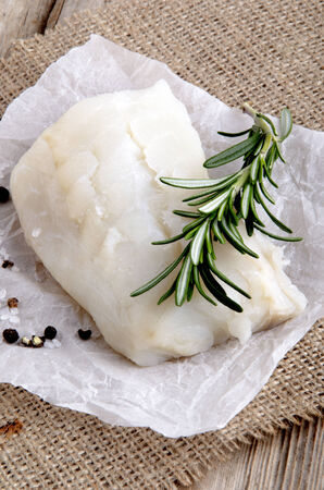 cod filled with rosemary, salt and pepper on kitchen paper photo