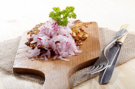 hash browns: patate fritte con rafano grattugiato su una tavola di legno