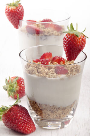 creamy yogurt with honey toasted oat and fresh organic strawberry in a glass photo