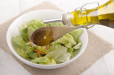 extra virgin olive oil: extra virgin olive oil is poured into a bowl with fresh salad