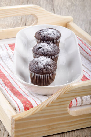 serving tray: chocolate cupcake with powdered sugar on a serving tray