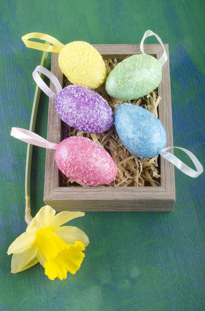 easter eggs and daffodil in a box filled with straw photo