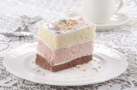 three layer: three layer cake with coloured sprinkle on a plate Stock Photo