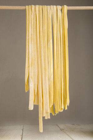 homemade tagliatelle on a wooden stick to dry photo