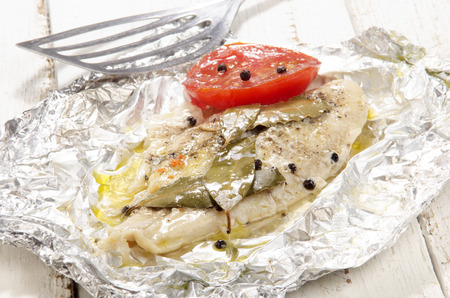 pangasius: baked pangasius with pepper and tomato in tin foil Stock Photo
