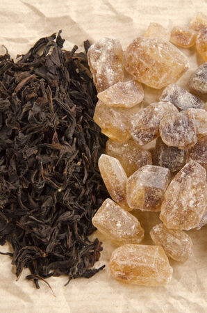 brown rock candy sugar and black tea on brown paper photo