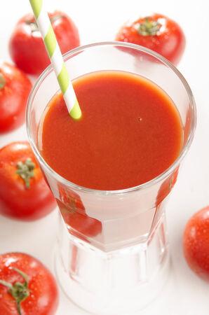 jugo de tomate: jugo de tomate con la paja en un vaso