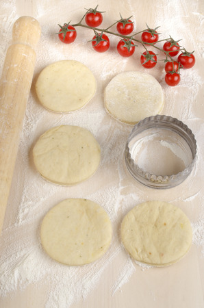 mini pizza: spicy mini pizza dough on a floury wooden board