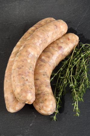casing: grill sausage with herbs in natural casing with thyme on a slate plate