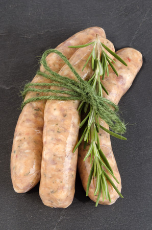 casing: grill sausage with herbs in natural casing and rosemary Stock Photo