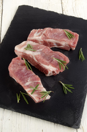 raw ribs with rosemary on slate plate photo