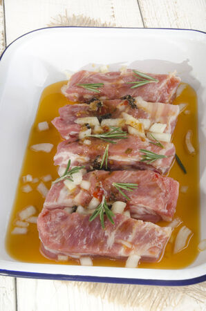 ribs with rosemary and marinade in a bowl photo