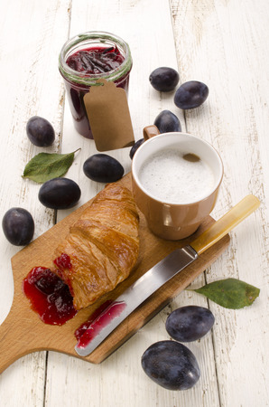 breakfast with croissant, plum jam and cafe au lait photo