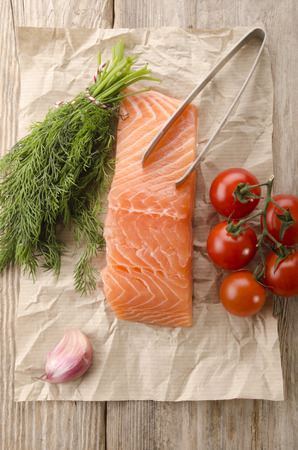 raw salmon fillet with dill, garlic, tomato and fishbone tong on brown kitchen paper photo