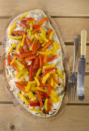 tarte flambee with yellow paprika, red bell pepper stripes, onion and sour cream