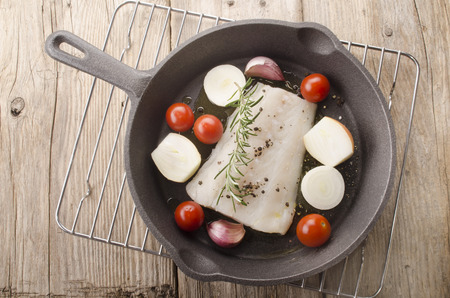 cast iron pan: cod fillet with tomato, garlic, onion, rosemary and crushed pepper in a cast iron pan Stock Photo