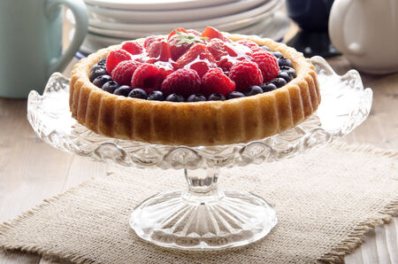 flan case with blueberries, strawberries, raspberries on a glass cake stand photo