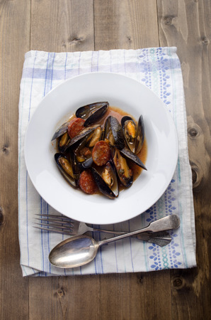 warm mussel with tomato chorizo sauce on a plate photo