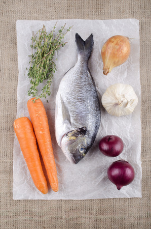 sea bream: raw sea bream with carrot, thyme, onion and garlic on white kitchen paper