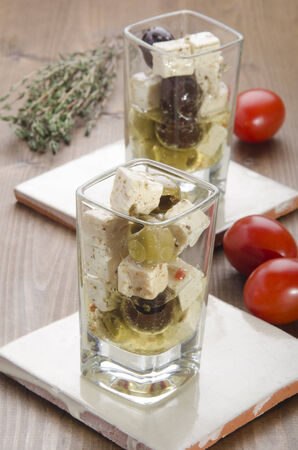 cubed: mediterranean salad, made with olive, spices and cubed goat cheese in a shot glass