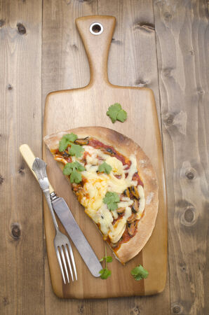sea food: sea food pizza with fresh coriander, knife and fork on wooden board