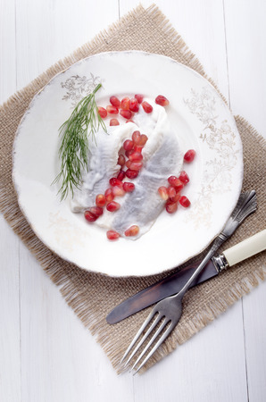 dill seed: herring with sour cream, pomegranate seed and dill on a plate