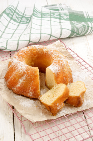 powdered sugar: home baked gugelhupf with powdered sugar on brown paper and tea towel in the background Stock Photo