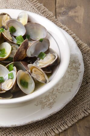 wine sauce: cooked clams in wine sauce with spring onion in a bowl